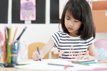 Mädchenzeichnungsfarbe zeichnet im Kindergartenklassenzimmer-, Vorschul- und Kinderbildungskonzept Standard-Bild - 83607861