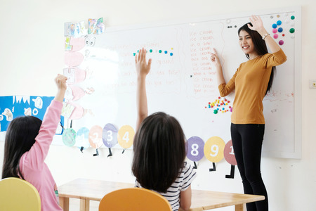 Young woman teacher teaching kids in kindergarten classroom Stockfoto