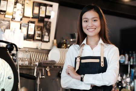 Young asian women Barista standing with smiling face in font of cafe counter background, small business owner, food and drink industry concept Imagens