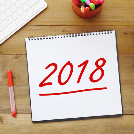2018 on notebook paper at office table background new year banner concept stock photo