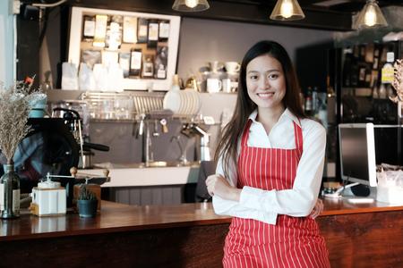 젊은 아시아 여성 카페 카운터 배경, 중소 기업 소유자, 음식과 음료 업계의 개념의 글꼴에 얼굴을 웃 고 함께 서있는 바리 스타