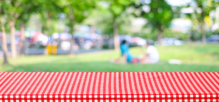 Empty table with red checked tablecloth over blur park with people and bokeh background, banner, food and product display montage Stock Photo