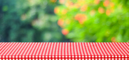 Empty table with red tablecloth over blur green tree and bokeh background, for food and product display montage background, banner Stock Photo