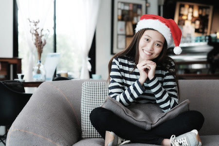 winter fashion: Cute asian girl wearing Christmas hat with smiling face sitting on sofa, Merry Christmas and happy new year concept