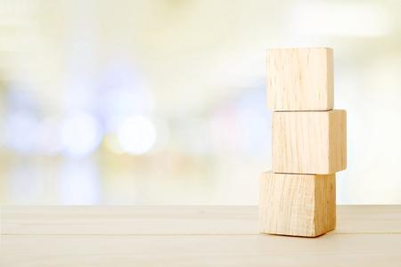 덩어리 죠 테이블 위에 3 개의 나무 큐브 추상 bokeh 밝은 배경, 텍스트 복사 공간 배너