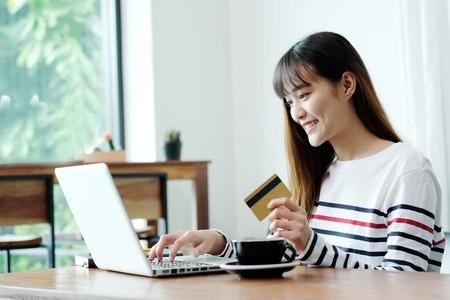 Mujer asiática joven que sostiene la tarjeta de crédito y que usa el ordenador portátil para hacer compras en línea en concepto del café, del negocio y de la tecnología, márketing digital, forma de vida casual