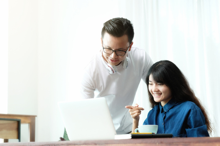 Young asian couple, man and woman, using and pointing laptop computer screen in casual   lifestyle, technology and lifestyle Imagens