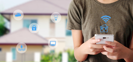Woman using smart phone as smart home remote control mobile app over blurred house background, banner, smart home device wireless network, the internet of things concept