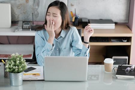 Junge asiatische gähnende Geschäftsfrau beim Arbeiten mit Laptop-Computer im Büro, Frau im zufälligen Bürolebensstilkonzept Standard-Bild