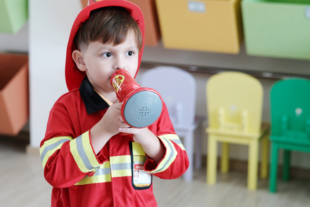 Boy playing as fireman police occupation in kindergarten class, kid occupation, education concept 免版税图像