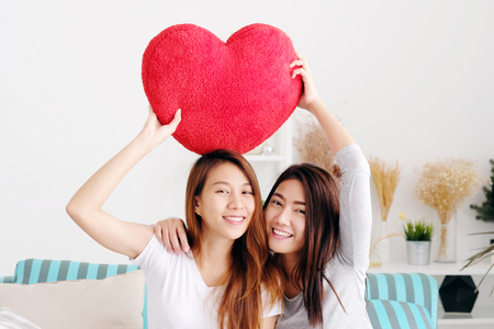 Young cute asia lesbians holding red heart shape willow together smiling with happiness at home, LGBT, couple lesbians, valentine's day concept