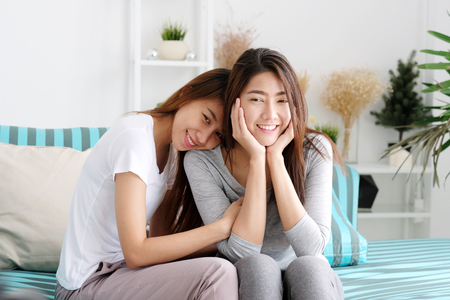 Young cute asia lesbian couple happy moment while sitting on spfa in living room, lgbt, homosexual, lesbian couple lifestyle