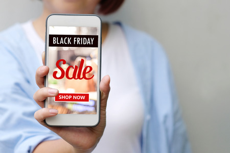 Hand holding smart phone with black friday online sale on screen device over blur store background, business and technology, online shopping promotion, digital marketing concept