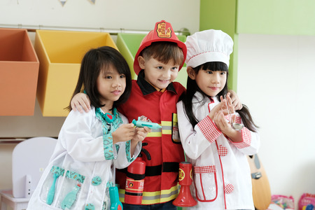 Cute boy and girls playing as fireman, doctor and cook occupation in kindergarten class, kid occupation, education concept Stockfoto