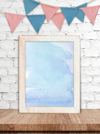 Blank white wooden frame with blue abstract watercolor painting background on wood table and party flags on white brick wall background, copy space for text, mock up Foto de archivo