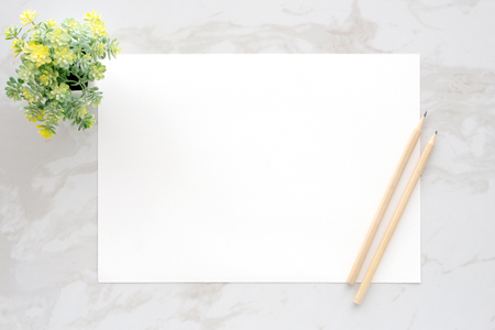 Blank white note paper and pencils on white marble background, flat lay, top view, template