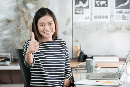 Young asian businesswoman thump up and smiling while sitting at her desk office, positive expression, sucess in business concept