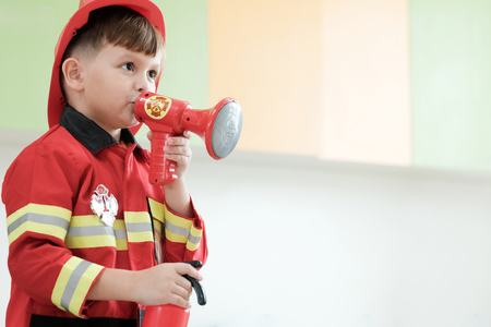 Boy playing as fireman police occupation in kindergarten class, kid occupation, education concept Stock Photo