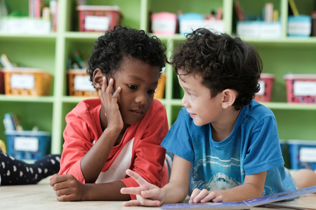 American and African boys are reading together with happiness in their kindergarten classroom, kid education and diversity concept Stock Photo