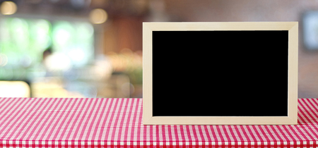 Blank chalkboard standing on table over blur store with bokeh background, space for text, mock up, product display montage