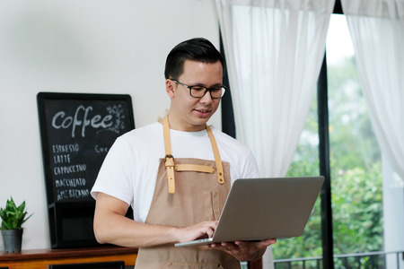 Young asian man, barista, using laptop computer at cafe background, food and drink concept Stock Photo