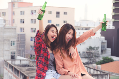 Two asian women drinking at rooftop party, outdoors celebration, LGBT couple Фото со стока