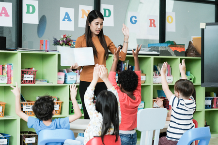 Young asian woman teacher teaching kids in kindergarten classroom, preschool education concept Stock Photo