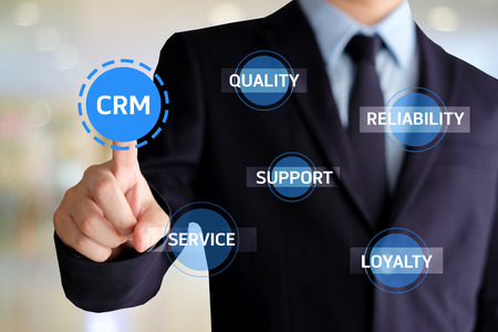 Businessman hand touch CRM, Customer Relationship Management, icon over blur background, success in business concept