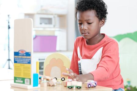 Portret van Afrikaanse jongen ongelukkig emotioneel zittend in de klas van de kleuterschool, divers onderwijsconcept voor kinderen