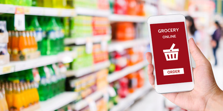 Hand holding smartphone with grocery online shopping application on device screen over blur supermarket background, business and technology, lifestyle concept