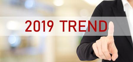 Mano de la empresaria tocando la tendencia 2019 sobre desenfoque de fondo de la oficina, banner, plan anual de estrategia empresarial 2019, éxito en el concepto empresarial