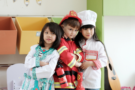 Boy and girls playing as fireman police, doctor and chef occupation in kindergarten class, kid occupation, education concept 스톡 콘텐츠