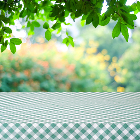 Empty table with green and white tablecloth over blurred park nature background, for product display montage, spring and summer