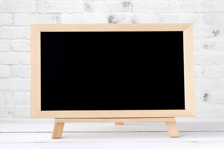 Blank chalkboard standing on white table over white brick wall background, space for text