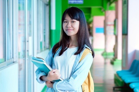 Asian student girl holding books and carry school bag while walking in school campus background, education, back to school concept