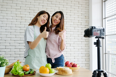 Two young asian woman food bloggers talking and thumb up while recording video, vlog concept, people, food and technology communication Banque d'images
