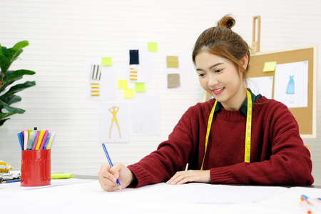Young asian woman fashion designer working in studio with happiness emotion, small business owner, fashion industry concept Banco de Imagens - 115936099