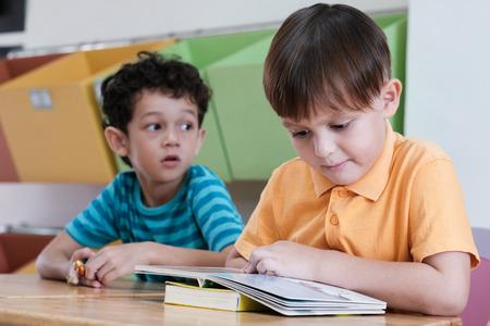 Livre de lecture de garçon dans leur classe de maternelle, concept d'éducation d'enfant