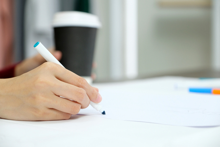 Close up of woman hand holding blue pen over white paper on table desk background Stok Fotoğraf