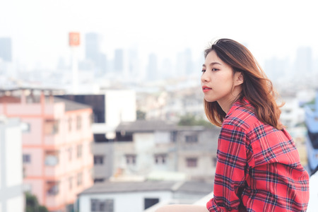 Young asian woman sitting and smiling at rooftop outdoor in urban city background, happy lifestyle Stockfoto