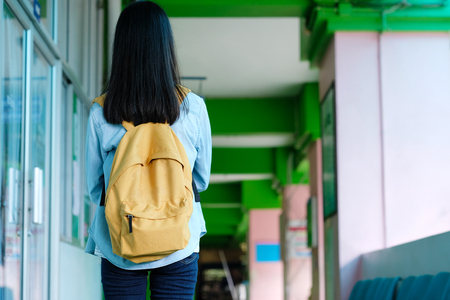 Back of student girl holding books and carry school bag while walking in school campus background, education, back to school concept Stock Photo
