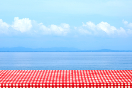 Empty table with red and white tablecloth over blurred sea outdoor nature background, for product display montage, spring and summer