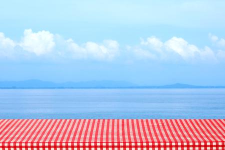Mesa vacía con mantel rojo y blanco sobre fondo de naturaleza al aire libre de mar borroso, para montaje de exhibición de productos, primavera y verano