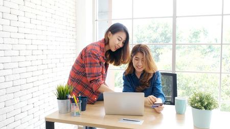 Due giovani donne asiatiche in possesso di carta di credito e utilizzando il computer portatile per lo shopping in linea con il concetto di felicità, business e tecnologia, marketing digitale, stile di vita casual Archivio Fotografico