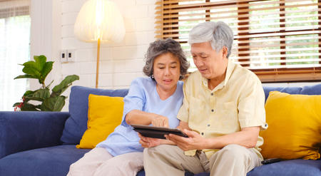 Happy senior asian couple using digital tablet computer sitting on sofa at home living room background, senior people and technology lifestyles Stock Photo