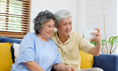 Happy senior asian couple taking selfie at home living room, active senior people in happy moment, casual retirement people with technology and lifestyle Imagens