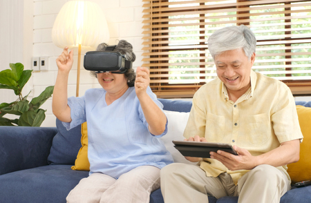 Senior asian couple playing virtual reality headset and using digital tablet in home living room with happiness emotion, retirement lifestyle and technology