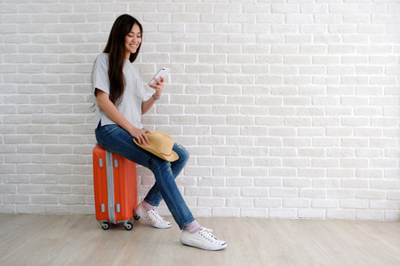 Young asian woman traveler holding smart phone and sitting on luggage in white room with copy space, people summer holiday vacation background concept
