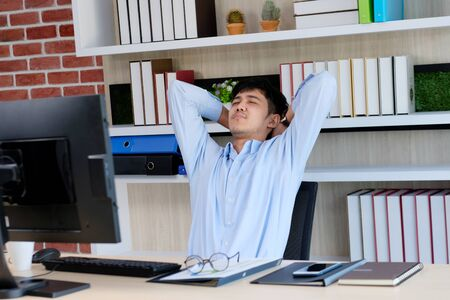 Young asian office man stretching body for relaxing while working with computer at his desk, office lifestyle, business situation
