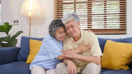 Älteres asiatisches Paar, das sich gegenseitig aus depressiven Emotionen tröstete, während es auf dem Sofa zu Hause im Wohnzimmer sitzt, alter Ruhestandslebensstil